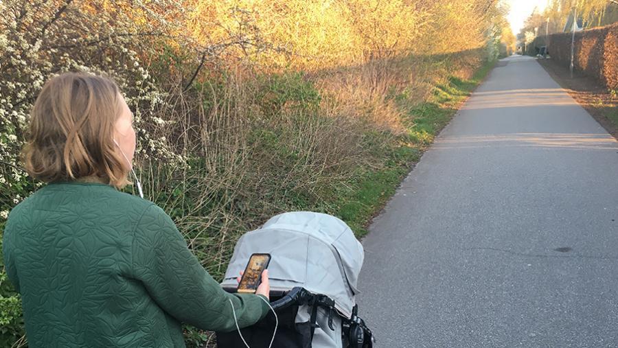 Kvinde der går med en barnevogn og hører lydbog