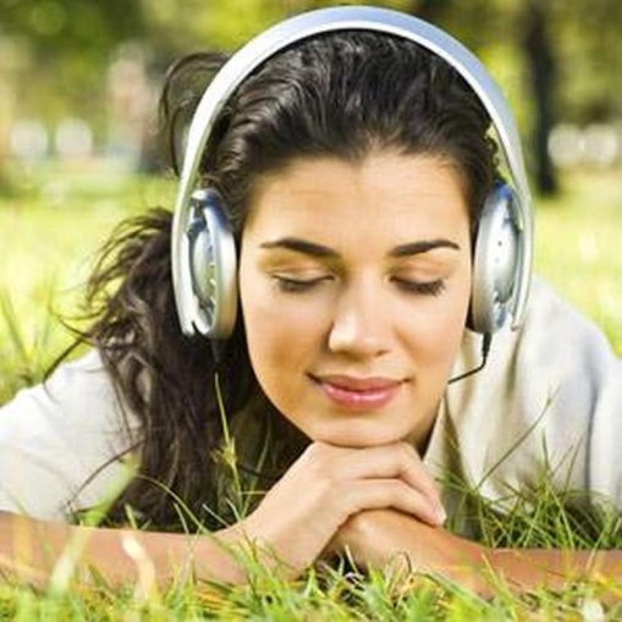 Pige med hovedtelefoner på liggende i græsset