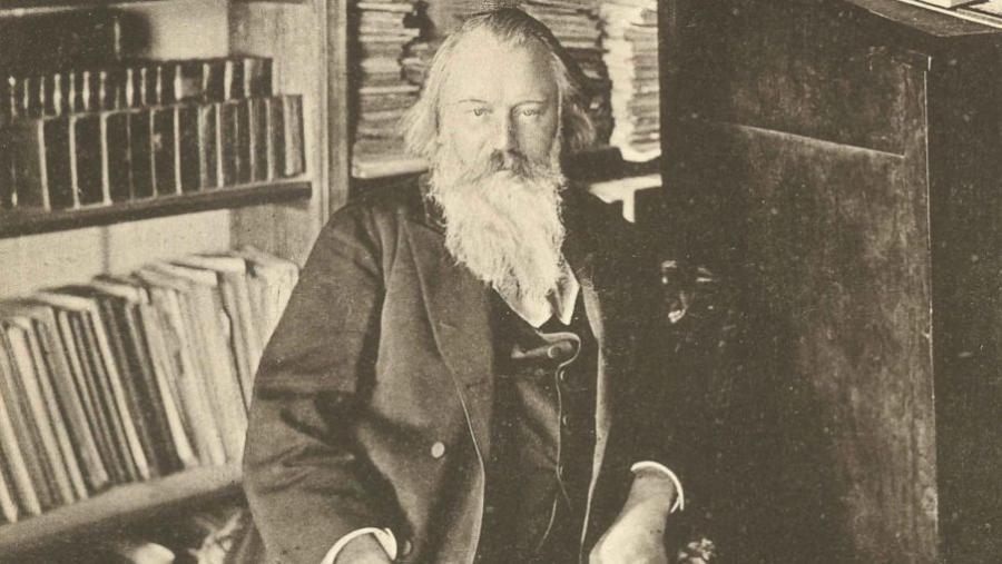 Gammelt foto af komponisten Johannes Brahms siddende omgivet af bøger